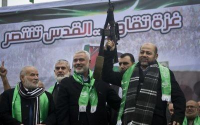 Les dirigeants du Hamas de Gaza Ismail Haniyeh, (au centre) et Mousa Abu Marzouq, à droite, brandissent une arme et saluent leurs partisans pendant une cérémonie marquant le 27e anniversaire de la création du mouvement islamiste le 14 décembre 2014 dans la ville de Gaza. (Crédit : AFP / MAHMUD HAMS)