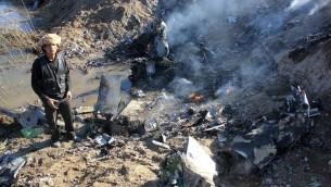 Un combattant de l'Etat islamique collecterait des pièces à partir des restes d'un avion de guerre jordanien de la coalition dirigée par les Etats-Unis qui a été abattu dans la région de Rakka en Syrie, le 24 décembre 2014. (Crédit : AFP/RMC/STR)