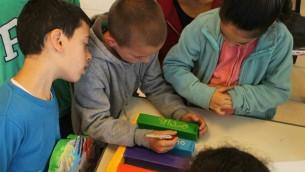 Des élèves de Hand in Hand en train de fabriquer la menorah destinée à la Maison blanche (Crédit : Hand in Hand)