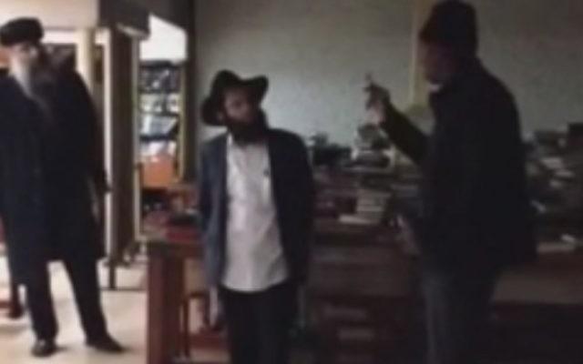 L'agresseur présumé, à droite, échange des mots avec un homme juif à l'intérieur du siège de Chabad à New York le 9 décembre, 2014. (Capture d'écran: YouTube)