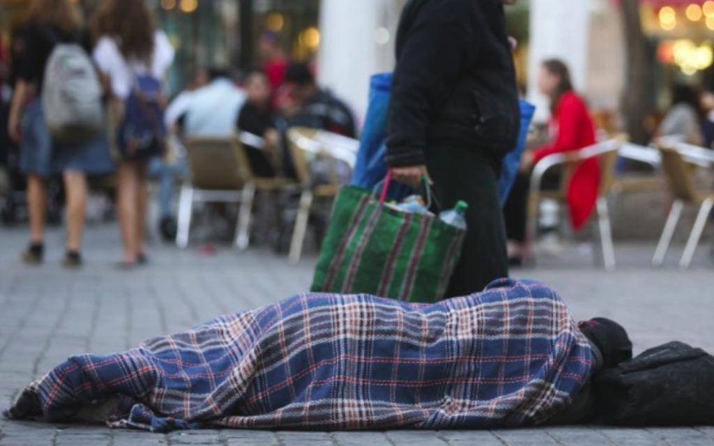 Les gens passent devant un homme sans-abri qui dort dans la rue, dans le centre de Jérusalem, le 10 novembre, 2013. (Crédit : Nati Shohat / Flash90)