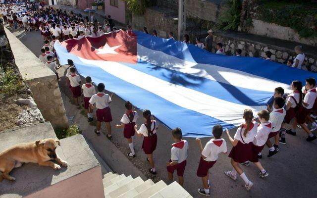 De jeunes élèves portant le drapeau cubain lors d'un défilé dans les rues de Gibara à Cuba le 20 janvier 2014 (Crédit : Moshe Fai/Flash90))