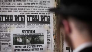 """Un Juif ultra-orthodoxe lisant un """"Pashkvil"""" - une affiche d'information - dans le quartier de Méa Shearim, le 19 août 2014 à Jérusalem (Crédit photo: Yonatan Sindel / Flash90)"""