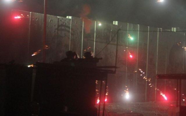 La police des frontières israélienne et un soldat affrontent des Palestiniens au poste de contrôle de Qalandiya, le 24 Juillet, 2014. (Crédit : Issam Rimawi / FLASH90)