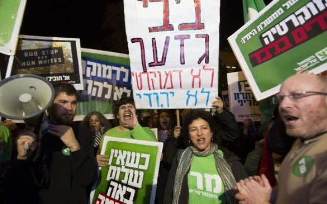 """Des militants tiennent des pancartes et des drapeaux alors qu'ils protestent contre le projet de loi sur  """"l'Etat juif"""" près de la résidence du Premier ministre à Jérusalem le 29 novembre, 2014. Certaines des pancartes qualifient Benjamin Netanyahu de raciste, et affirment qu'il cherche la démocratie pour les Juifs seulement . (Crédit : Yonatan Sindel / Flash90)"""