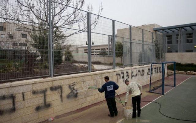 Les travailleurs nettoyant des graffitis racistes de l'école bilingue le 7 février 2012 (Crédit :  Flash90)