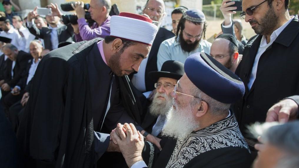 Rabbi Shlomo Amar (assis à droite) sert la main d'un imam lors d'une cérémonie où les leaders chrétiens et musulmans ont montré leur soutien envers la communauté juive suite à l'attaque d'Har Nof (Crédit : Yonathan Sindel/Flash90)