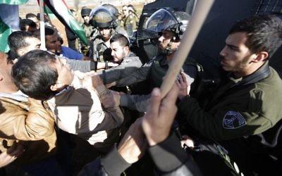 Un agent de la police des frontières attrape le fonctionnaire de l'AP (à gauche) lors d'une manifestation en Cisjordanie le 10 décembre (Crédit : AFP/Abbas Momani)