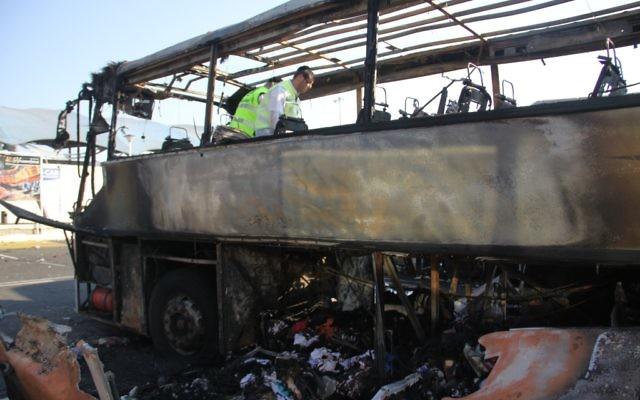 Une équipe examine les restes du bus bombardé supposément par le Hezbollah en juillet 2012 (Crédit : Dano Monkotovic/Flash90/JTA)