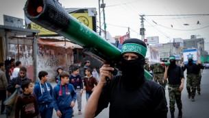 Une homme masqué du Hamas portant une fausse roquette (Crédit : Abed Rahim Khatib/Flash90)