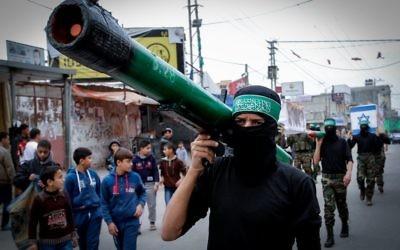 Un homme masqué du Hamas portant une fausse roquette (Crédit : Abed Rahim Khatib/Flash90)