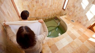 Une femme entrant dans le mikvé, le bain rituel juif  (Crédit : JTA / Mayyim Hayyim)