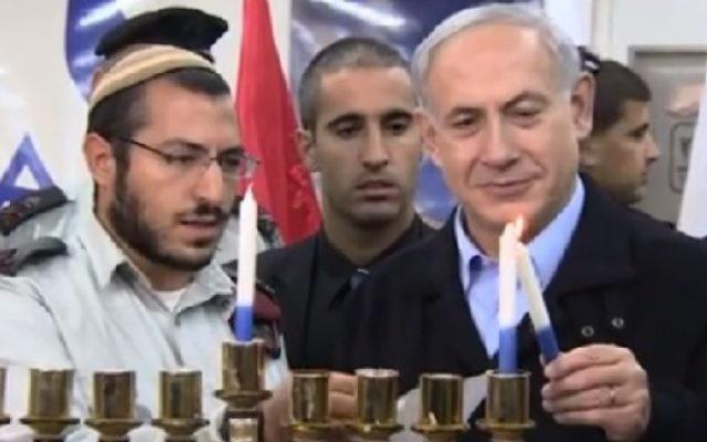 Benjamin Netanyahu allume la première bougie de Hanoukka en compagnie de soldats (Crédit : GPO)