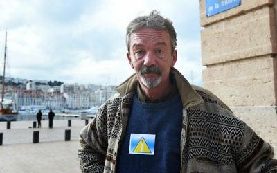 """Arnaud, un homme sans-abri, porte un """"badge de sécurité"""" lors d'une manifestation en face de l'Hôtel de Ville de Marseille, sud de la France, le 3 décembre, 2014. (Crédit : AFP / Anne-Christine Poujoulat)"""
