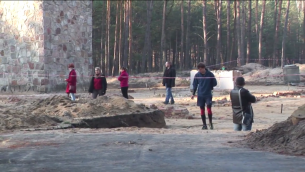 À l'ancien camp d'extermination nazi de Sobibor, en Pologne orientale, un visiteur se promène avec son chien vers la zone des chambres à gaz récemment excavées - 11 novembre 2014. (Crédit : Lena Klaudel)