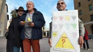 """Un manifestant tient un signe en face de l'Hôtel de Ville de Marseille, sud de la France, le 3 décembre 2014, lors d'une manifestation contre un """"badge de sécurité"""", distribué aux personnes sans-abri à Marseille. (Crédit : AFP / Anne-Christine Poujoulat)"""