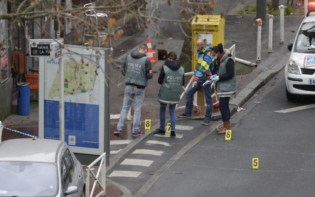 Des légistes de la police examinent la scène où une femme officier de police a été abattue à Montrouge, dans la banlieue sud de Paris le 8 Janvier 2015 (Crédit : AFP)