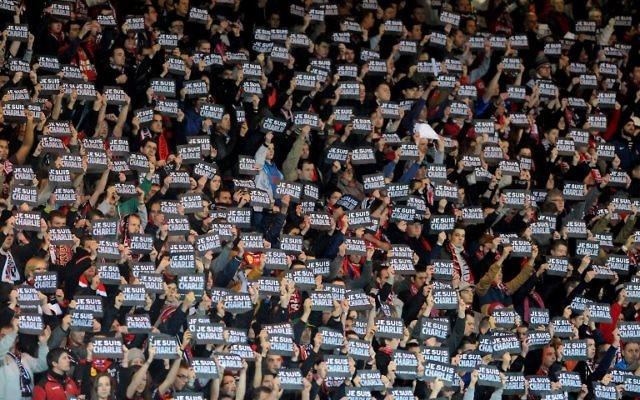 """Des supporters à un match de rugby brandissent une pancarte """"jesuischarlie"""" (Crédit : AFP)"""