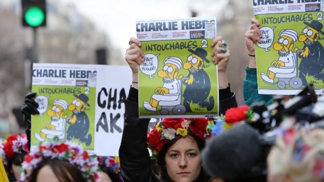 Des militantes Femen arborant les Une de Charlie Hebdo pendant la Marche républicaine le 11 janvier 2015 sur la Place de la République (Crédit: AFP/LOIC VENANCE)