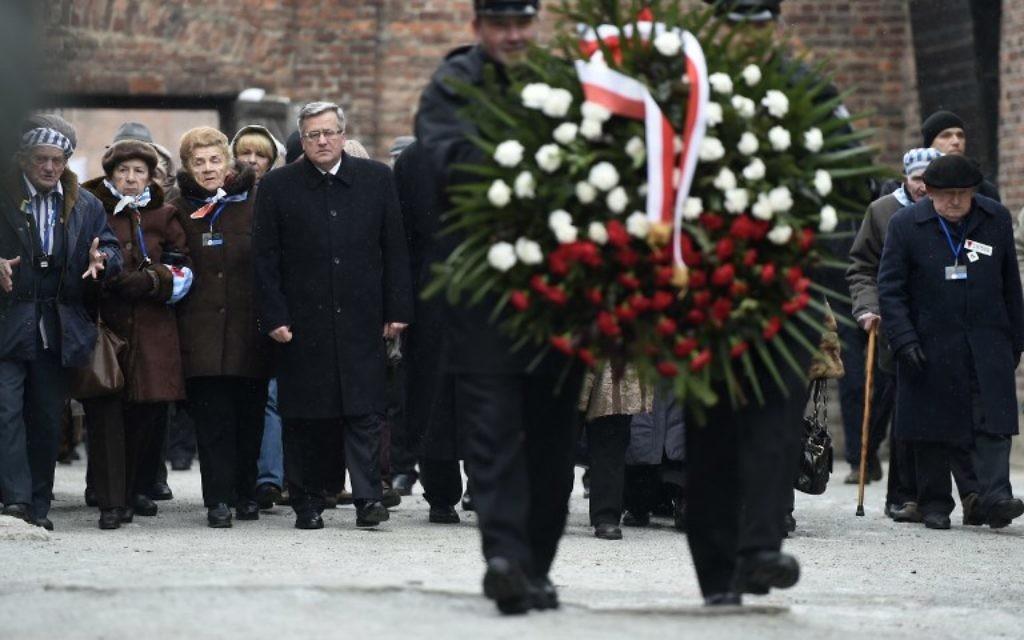 Le président polonais, Bronislaw Komorowski (au centre) et des survivants d'Auschwitz déposent une gerbe au mur de la mort de l'ancien camp de concentration d'Auschwitz le 27 janvier 2015 au mémorial d'Auschwitz-Birkenau à Oswiecim, Pologne. (Crédit : AFP PHOTO / ODD ANDERSEN)
