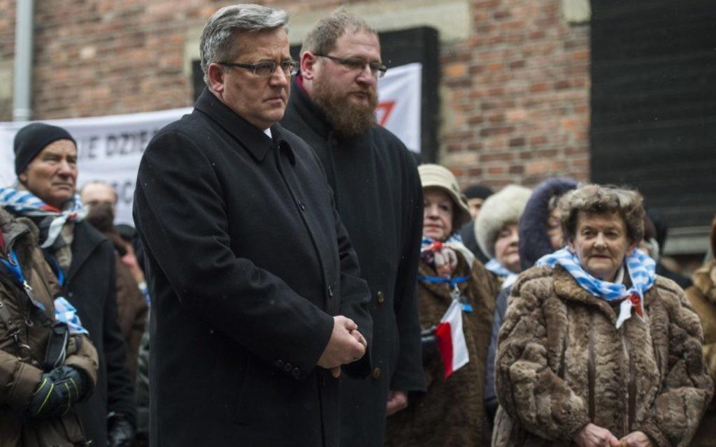 """Le président polonais Bronislaw Komorowski (CL), Piotr Cywinski (CR), directeur du musée d'Auschwitz-Birkenau et des survivants rendent hommage aux victimes des nazis à l'endroit de l'exécution """"du mur de la mort"""" dans l'ancien camp de concentration d'Auschwitz à Oswiecim, Pologne, lors du 70e anniversaire de la libération du camp de la mort nazi le 27 Janvier, 2015 (Crédit : AFP PHOTO / ODD ANDERSEN)"""