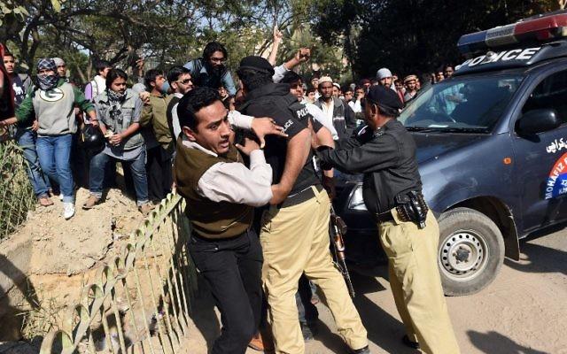 La police pakistanaise tentant d'empêcher les manifestant d'atteindre le consulat français à Karachi le 16 janvier 2015 (Crédit : ASIF HASSAN / AFP)