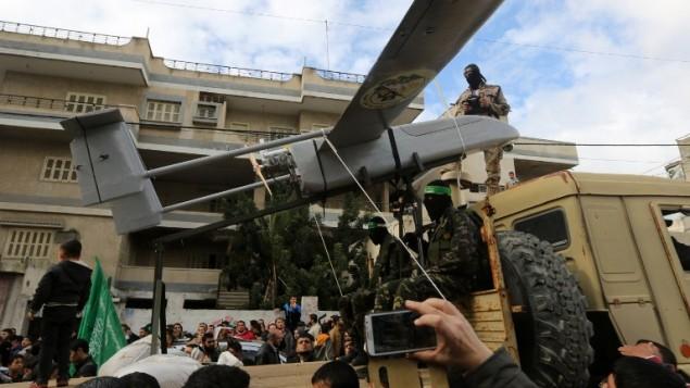 Les membres des brigades al-Qassam, la branche armée du Hamas, exposant un drone pendant une parade marquant le 27ème anniversaire du mouvement islamiste le 14 décembre 2014 dans la ville de Gaza  (Crédit : AFP/ MAHMUD HAMS)
