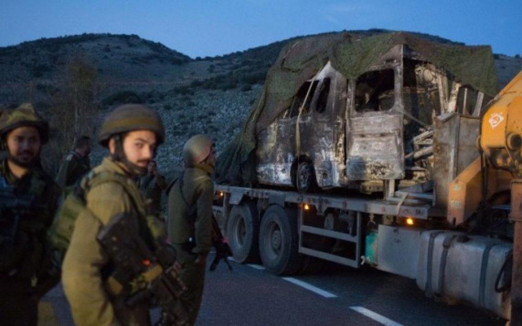 Des soldats israéliens regardent un véhicule brûlé près de Ghajar, après une attaque de missiles du Hezbollah le long de la frontière israélo-libanaise, le 28 janvier 2015. (Crédit : AFP/Menahem Kahana)