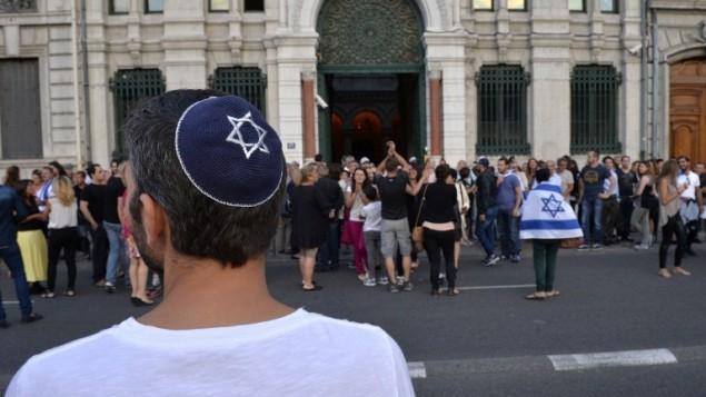 Un homme avec une kippa regarde les gens prendre part à une manifestation organisée par le CRIF devant la synagogue de Lyon, le 31 Juillet 2014. (Crédit : AFP/Romain Lafabregue)