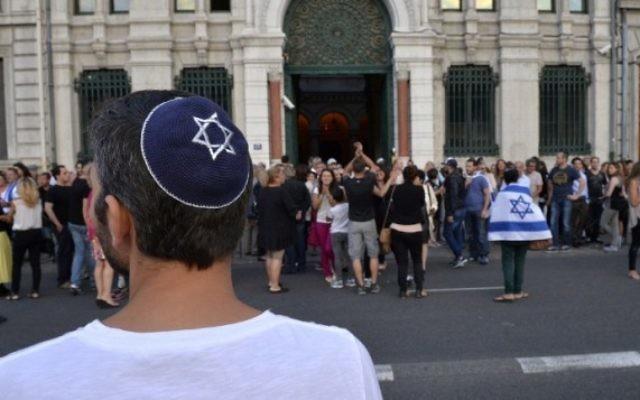 Un homme avec une kippa regarde les gens prendre part à une manifestation organisée par le CRIF devant la synagogue de Lyon, le 31 Juillet 2014. (Crédit : Romain Lafabregue/AFP)