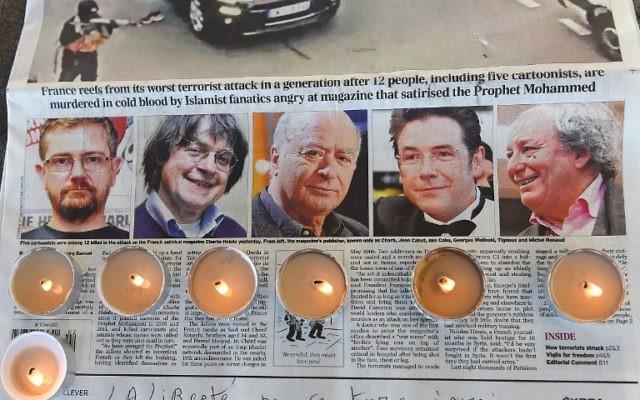 Des bougies placées sur un journal montrant les photos du rédacteur en chef et dessinateur de  l'hebdomadaire français satirique Charlie Hebdo Charb,, de Jean Cabut, alias Cabu, de Georges Wolinski et de Michel Renaud, tués la veille lors d'un attentat par deux hommes armés dans les bureaux du journal satirique français Charlie Hebdo, lors d'un rassemblement à Marseille, le 8 janvier 2015. (Crédit : Anne-Christine Poujoulat/AFP)