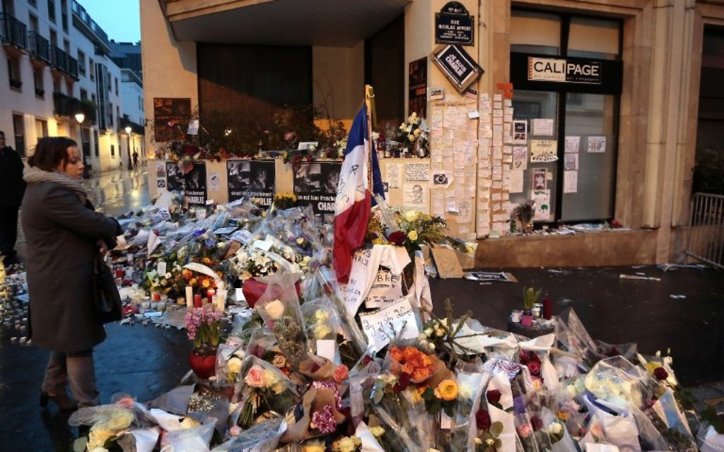 Une femme contemple les fleurs déposées devant les bureaux du magazine Charlie Hebdo à Paris pour les victimes du massacre du 7 Janvier (Crédit : AFP PHOTO /JACQUES DEMARTHON)