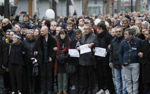 La dessinatrice Corinne Rey ( à gauche) connue sous le pseudonyme de Coco, une survivante de l'attaque de Charlie Hebdo, des membres du personnel,et des membres de la familles des victimes lors de la Marche Républicaine le  11 janvier 2015 à Paris (Crédit : AFP PHOTO / PATRICK KOVARIK)