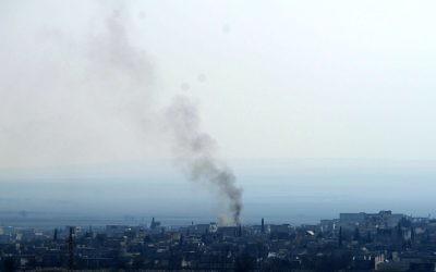 Une photo de la ville de Kobane prise le 26 janvier 2015 de la ville de Sanliufra d'où on peut voir de la fumée s'élever après les affrontements entre l'EI et les kurdes (Crédit : AFP)