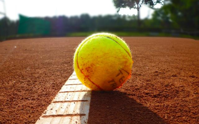 Illustration d'une balle de tennis sur un court de tennis de terre battue (Crédit : Pixabay)