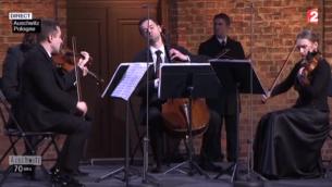 Capture d'écran France 2 - violonistes jouent avant la cérémonie à Auschwitz (Crédit : France 2)