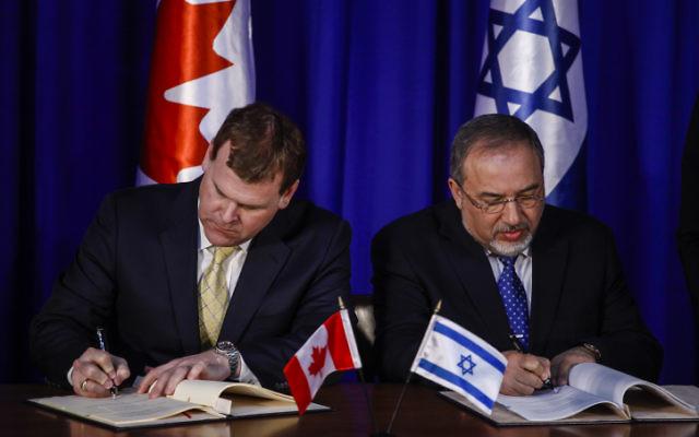 Le ministre israélien des Affaires étrangères, Avigdor Liberman, et le ministre canadien des Affaires étrangères, John Baird, signent un document - mardi 21 Janvier, 2014. (Crédit : Flash 90.)
