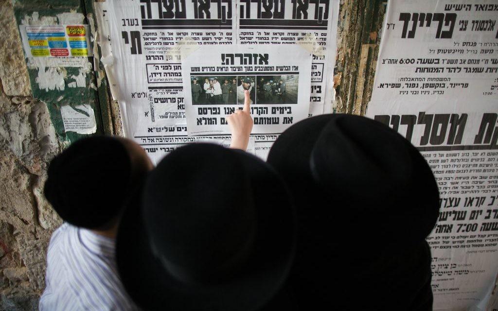Des Juifs ultra-orthodoxes lisent le journal dans une rue du quartier de Mea Shearim (Crédit : Yonathan Sindel/Flash 90)