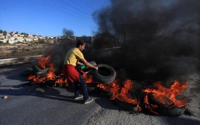 Un jeune Palestinien du camp de réfugiés Jilazoun brûle des pneus sur la route menant à Bet El, près de Ramallah lors d'affrontements avec des soldats israéliens 24 octobre 2014 (Crédit : STR / Flash90)