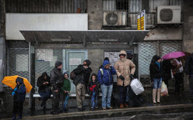 Israéliens vu attendant à un arrêt de bus dans le centre de Jérusalem tandis que la neige commence à tomber sur le premier jour de l'hiver. Le 7 janvier 2015. (Crédit : Hadas Parush / FLASH90)