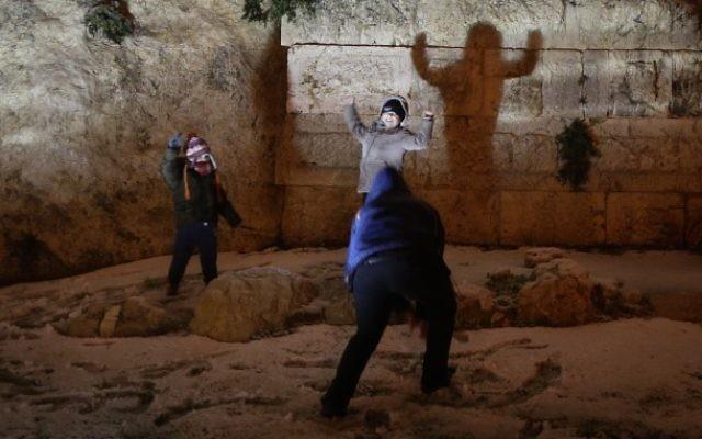 Des enfants jouent aux boules de neige à côté des murailles de la Vieille ville à Jérusalem (Crédit : Nati Shohat/Flash90)