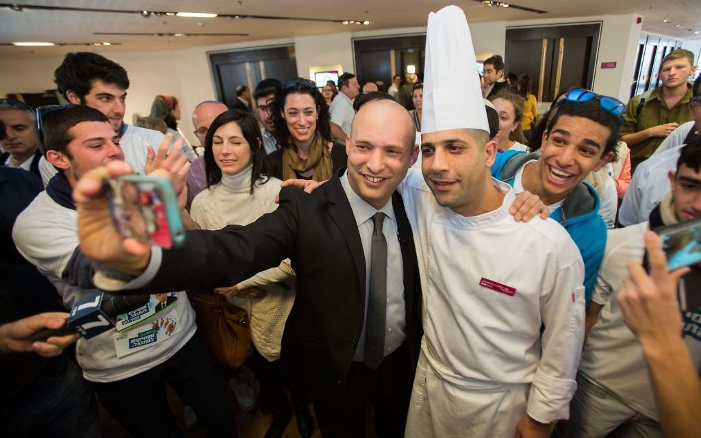 Le dirigeant de HaBayit HaYehudi, Naftali Bennett (celui qui ne porte pas la toque de cuisinier) avec ses supporters après avoir voté aux primaires de sont parti le 14 janvier 2015 (Crédit : Yonatan Sindel/Flash90)