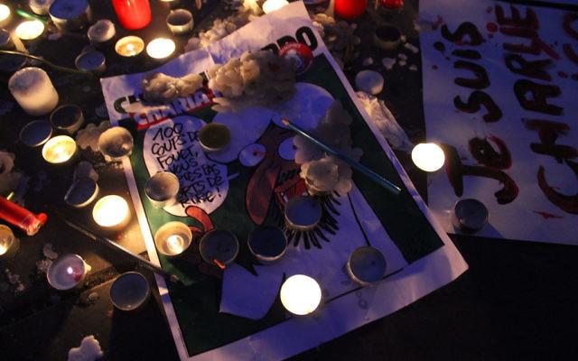 Une reproduction d'une caricature entourée de cierge pour commémorer la mort des dessinateur de Charlie Hebdo le 11 janvier 2005 (Crédit : Glenn CLoarec/Times of Israel)