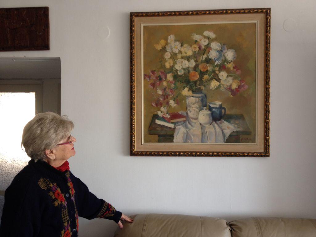Renée Gancz, survivante de l'Holocauste, admirant son tableau préféré dans son appartement de Tel-Aviv le 20 janvier 2015 (Crédit : Amanda Borschel-Dan/The Times of Israel)