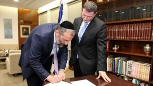 Le dirigeant du parti du Shas Aryeh Deri signant sa lettre de démission de la Knesset tandis que le président Yuli Edelstein observe le 30 décember 2014 (Crédit : Isaac Harari/porte parole de la Knesset)
