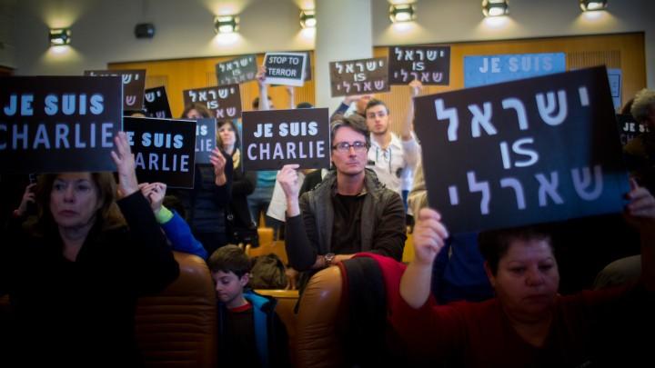 Les personnes tenant des panneaux lors de la cérémonie de commémoration à la mairie de Jérusalem ( Crédit : Yonatan Sindel/Flash90)