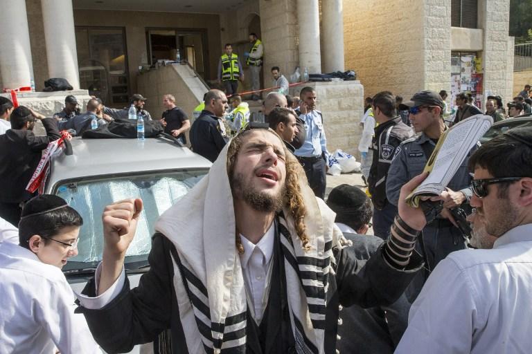 Un ultra orthodoxe prie sur les lieux de l'attaque terroriste de la synagogue d'Har Nof le 18 novembre 2014 (Crédit : AFP/Jack Guez)