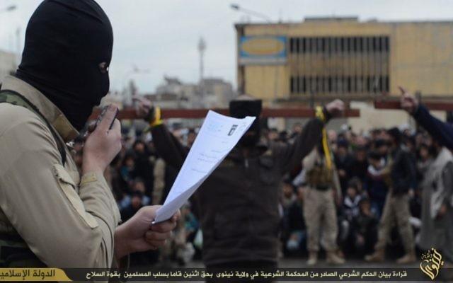 Un combattant de l'Etat islamique lisant les charges contre deux personnes crucifiées (en arrière plan) (Crédit : Capture d'écran)