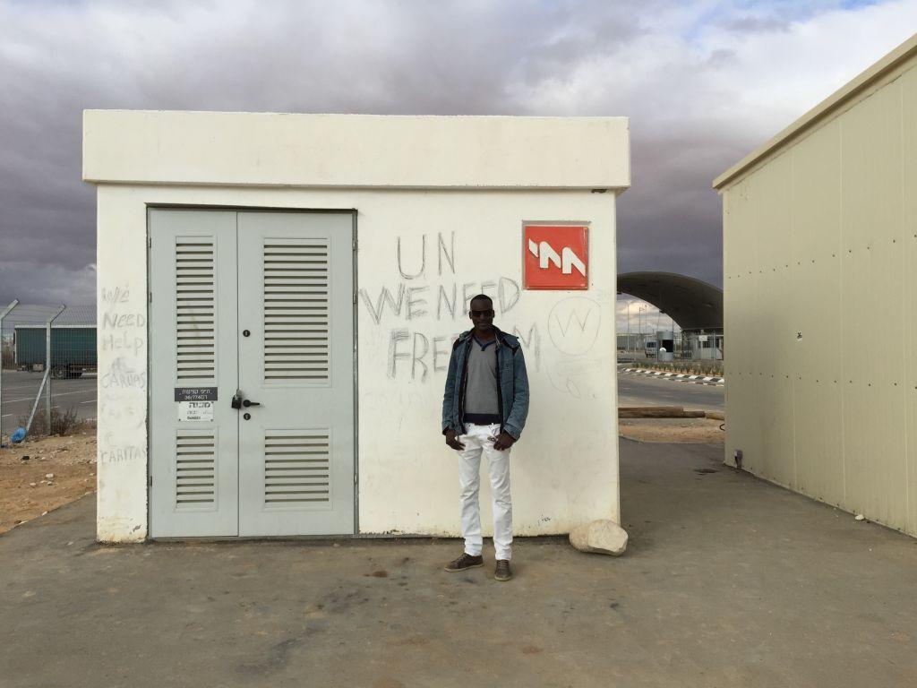 """Mutasim Ali près d'un mur à Holot où les detenus ont écrit en anglais """"ONU, nous avons besoin de liberté"""" (Crédit : Debra Kamin/Times of Israel)"""