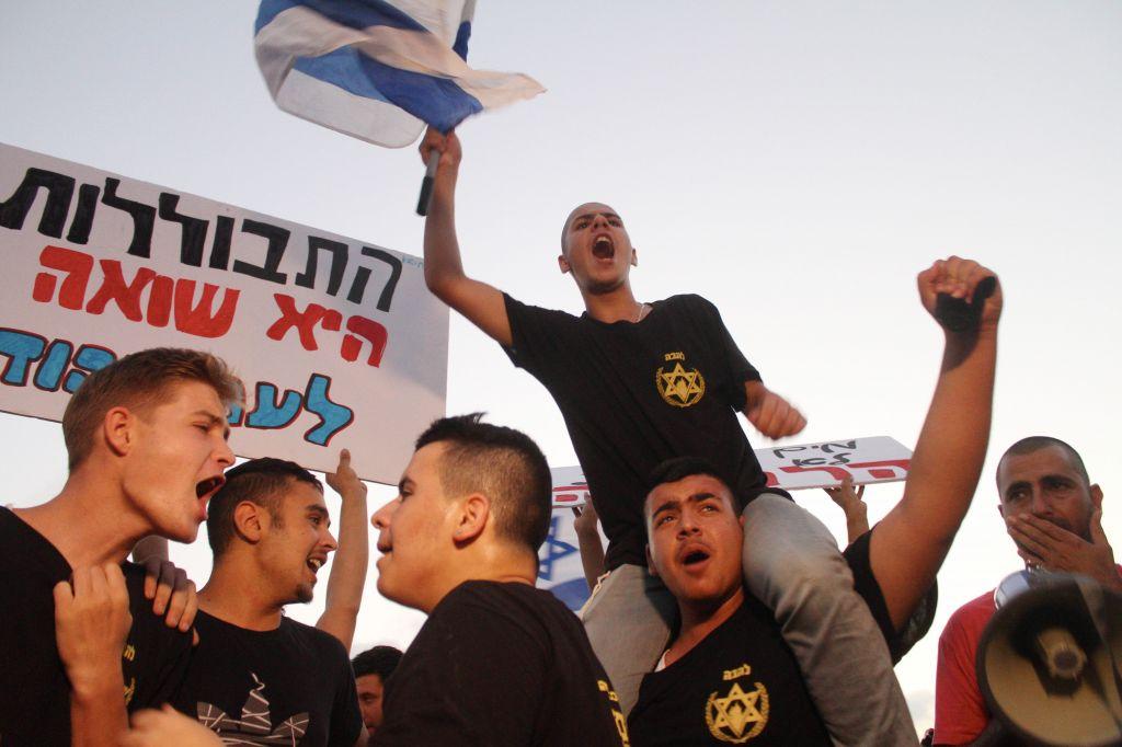 """Des jeunes de l'association Lehava avec des pancartes sur lesquelles on peut lire """"L'assimilation est un Holocauste"""" devant un mariage judéo-musulman près de Tel Aviv, le 17 août 2014. (Crédit : Flash90)"""